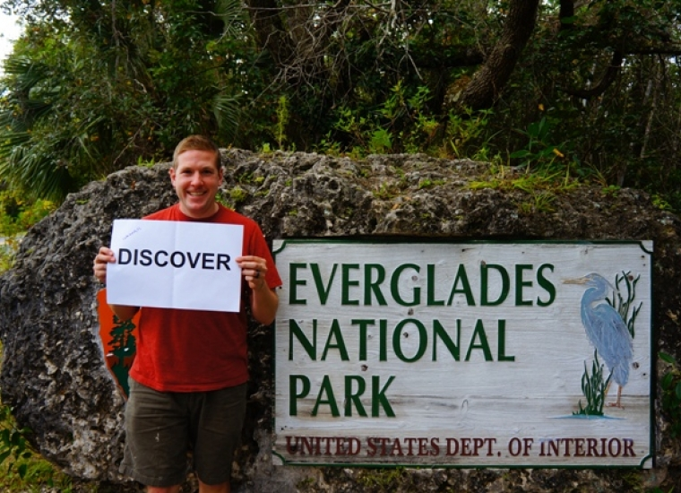 "Park visitor holding sign that says ""Discover"""