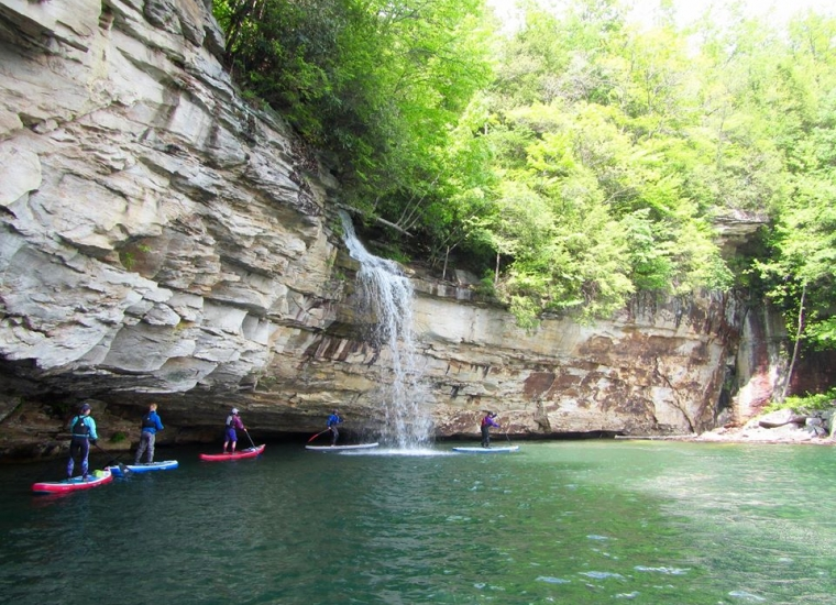 Three paddleboarders paddling near a small waterfall