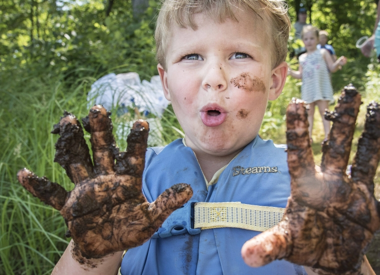 Child with muddy hands wearing life jacket