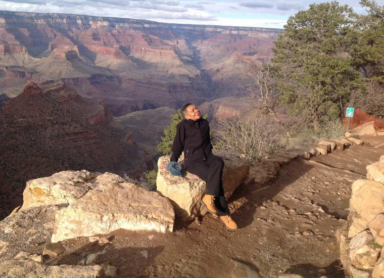Audrey Peterman sits on a rock on a plateau overlooking the Grand Canyon