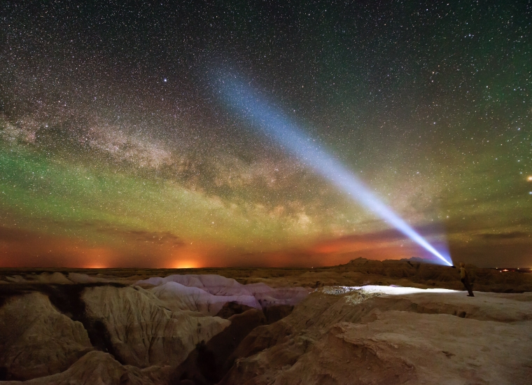 A man holds a flashlight toward the brilliant Milky Way at Badlands National Park