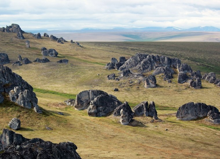In a vast undulating landscape, rocky outcrops populate the hillsides.
