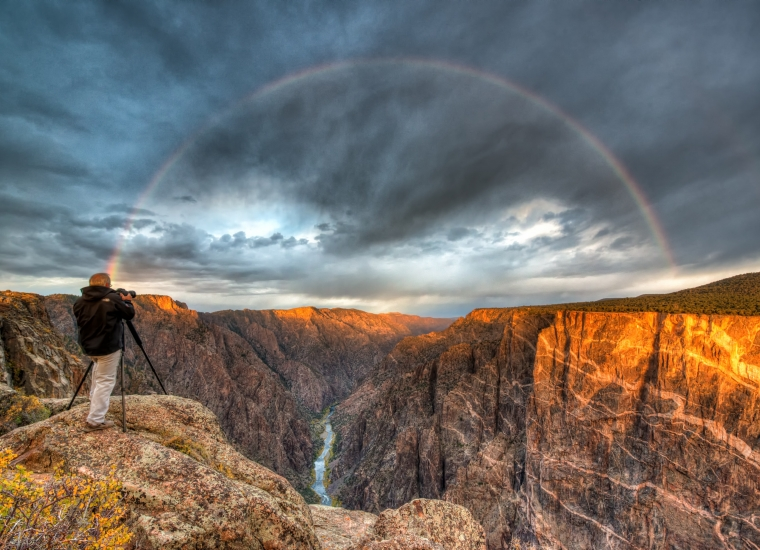 A man standing at the edge of the cliffs at Black Canyon of the Gunnison National Park with a rainbow with dark clouds during sunrise over the canyon