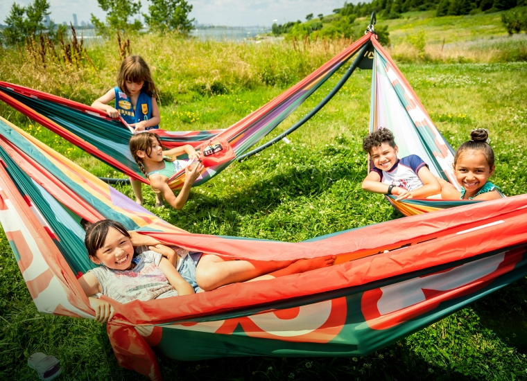A group of kids lounge in colorful hammocks