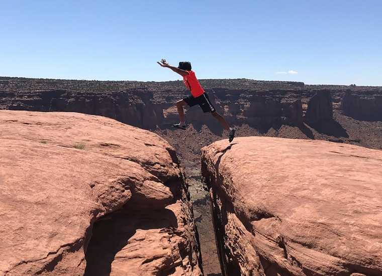 A man jumps between rocky plateaus