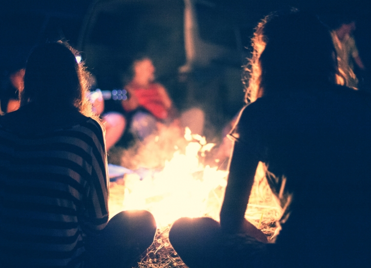 People gathered around a campfire at night