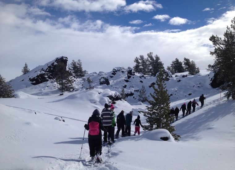 A group of people snowshoeing in a row at Craters of the Moon National Monument & Preserve