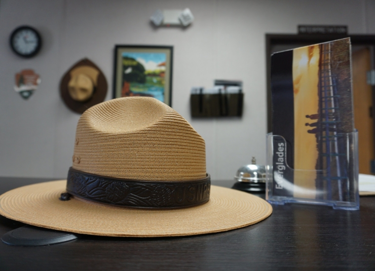 A ranger hat rests on a tabletop, next to a brochure on Everglades National Park