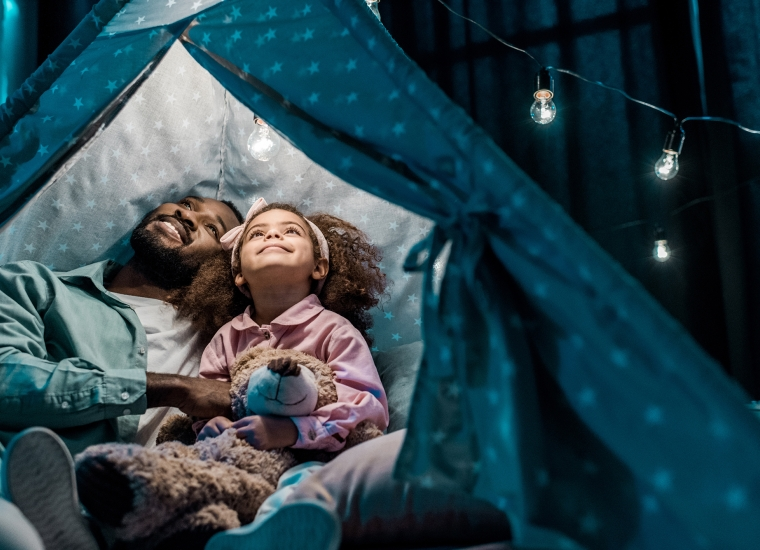 A father and daughter look up at an illuminated tent that is set up indoors