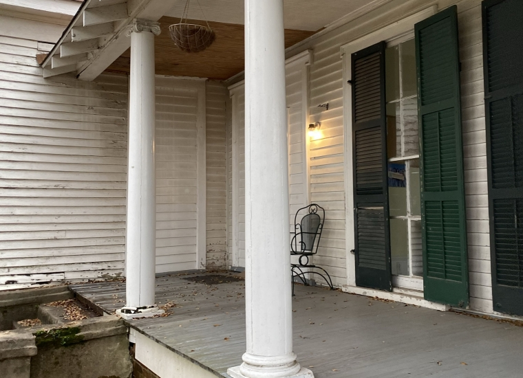 The covered front porch of a white house with green shutters