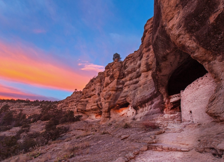 Colorful red, orange, and blue sunrise over the reddish cave dwellings at Gila Cliff Dwellings National Monument
