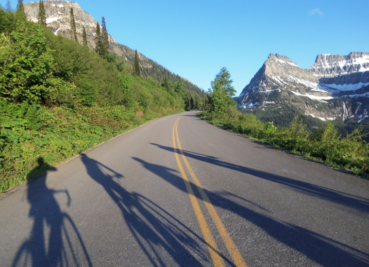 The shadow of 4 bikers on a paved road surrounded by green trees and snow-dusted grey mountains at Glacier National Park