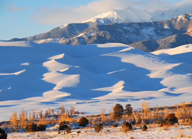 Snow-covered sand dunes in front of snowy mountains at Great Sand Dunes National Park and Preserve