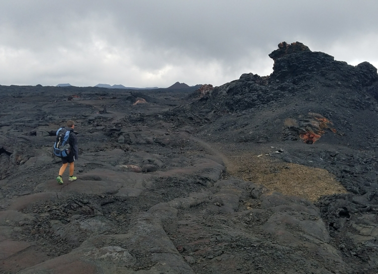 Backpacker hiking on black cooled lava along the Mauna Loa trail at Hawaii Volcanoes National Park