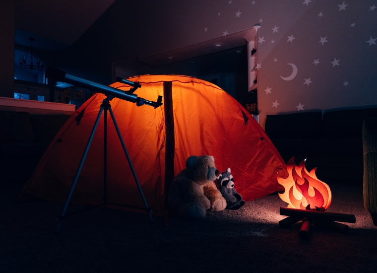 """A campsite set up indoors, with a paper """"campfire,"""" surrounded by stuffed animals (bear, raccoon), and an illuminated red tent. A small telescope points away toward the sky in the distance. Stars are projected on the walls."""