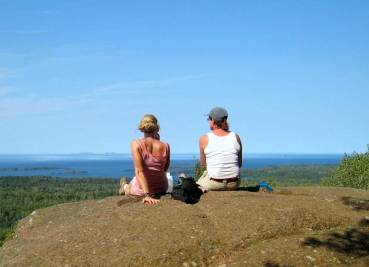 Two women sitting on a rock overlooking where the forest and blue water of Isle Royale National Park meet.
