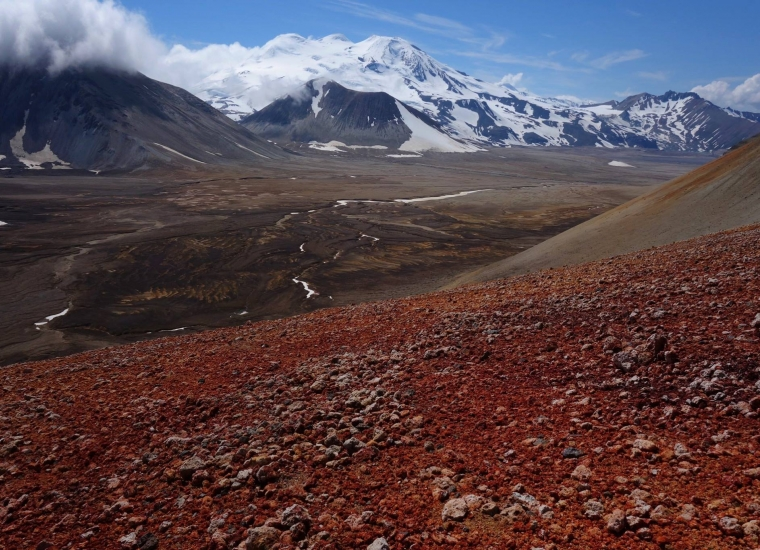 Red rocks on volcanic slopes in front of a brown valley with snow-covered mountains in the back