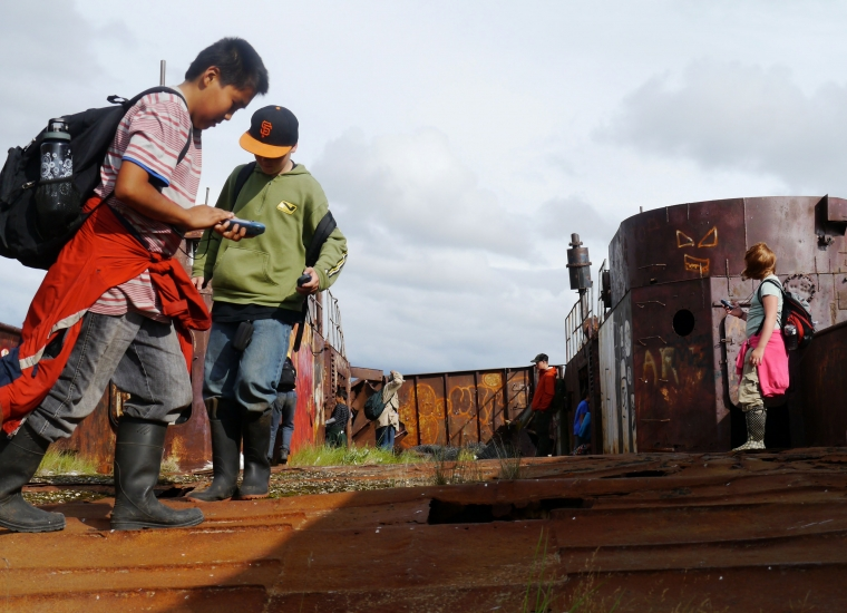 Students exploring a broken down barge while using GPS to try and find a geocache hidden somewhere at Kobuk Valley National Park