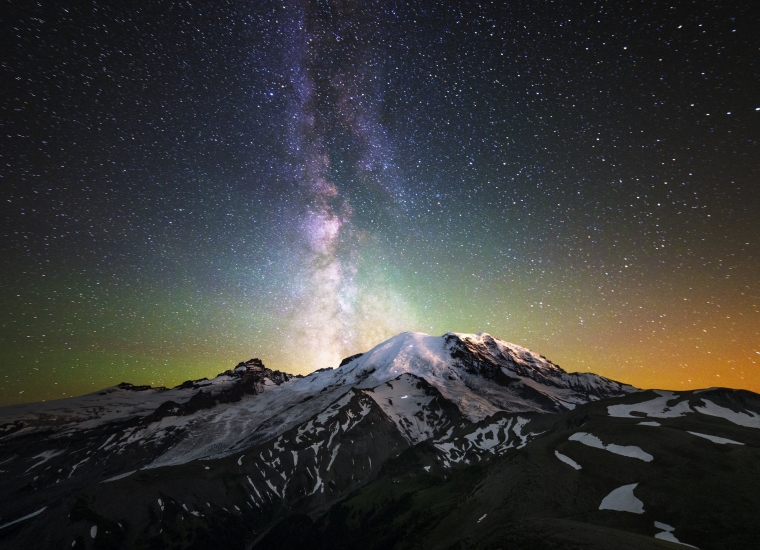The Milky Way glows brightly behind Mount Rainier