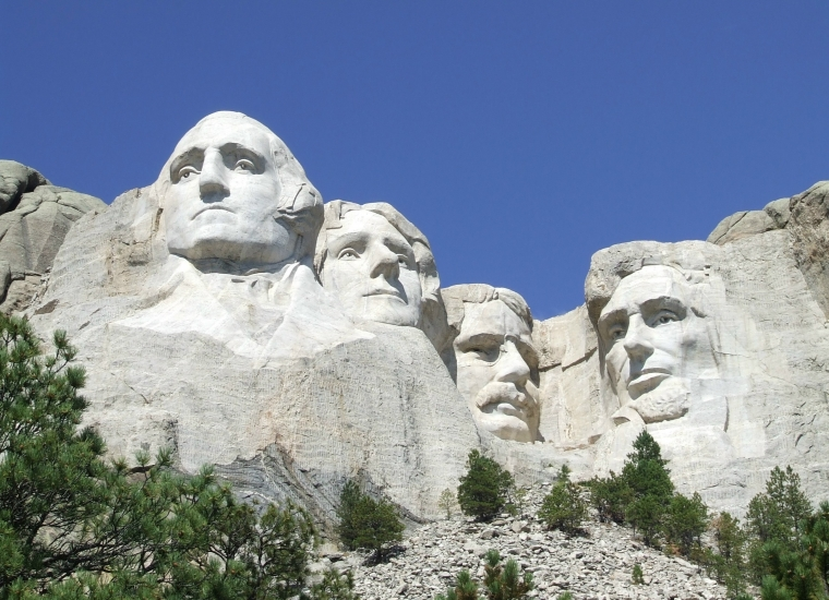 The faces of George Washington, Thomas Jefferson, Theodore Roosevelt and Abraham Lincoln carved into white stone under blue sky at Mount Rushmore National Monument
