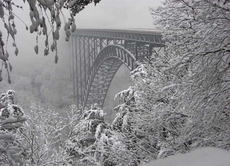 Fresh snow powders the steel bridge as well as the ground and the surrounding evergreen trees