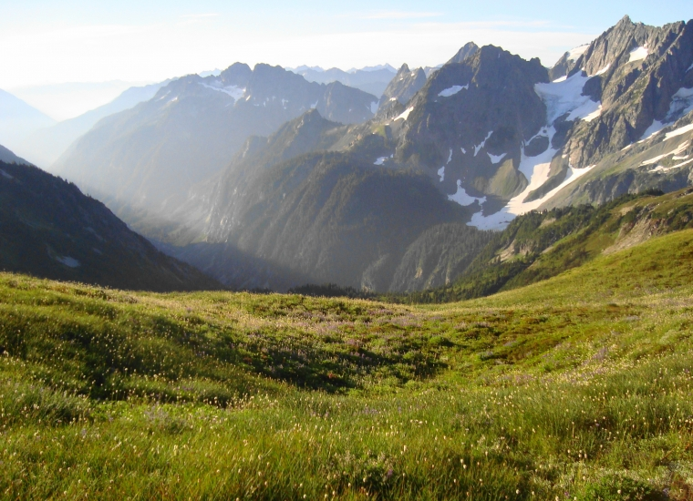 A green meadow in the foreground transitions to jagged, snow-covered mountains surrounding a steep valley