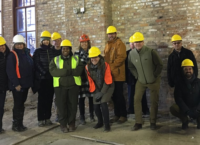 A group of employees wear construction hats and high-visibility vests and pose for a picture against a red brick wall.
