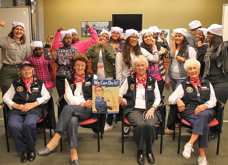 A group of young girls behind 4 elderly women, Rosie's of WWII, at Rosie the Riveter / WWII Home Front National Historical Park