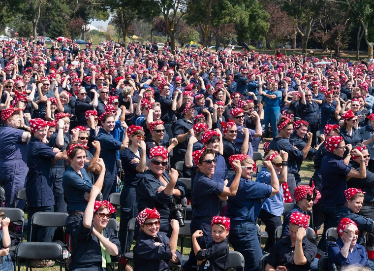 A large group of people dressed like Rosie the Riveter in red and white bandanas and blue work suits at the Rosie Rally at Rosie the Riveter WWII Home Front National Historical Park