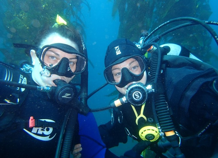 Two scuba divers, submerged under water, pose for a photo