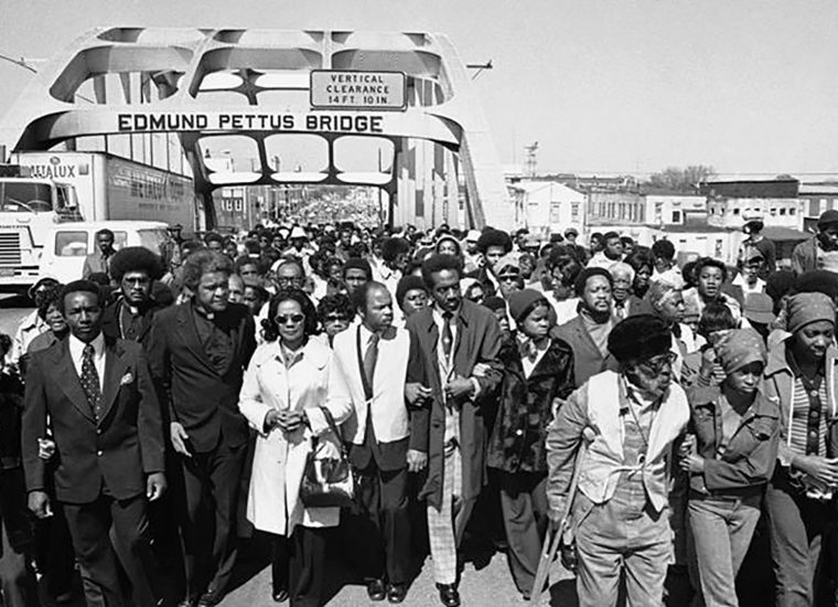 A group of protesters march across the Edmund Pettus Bridge