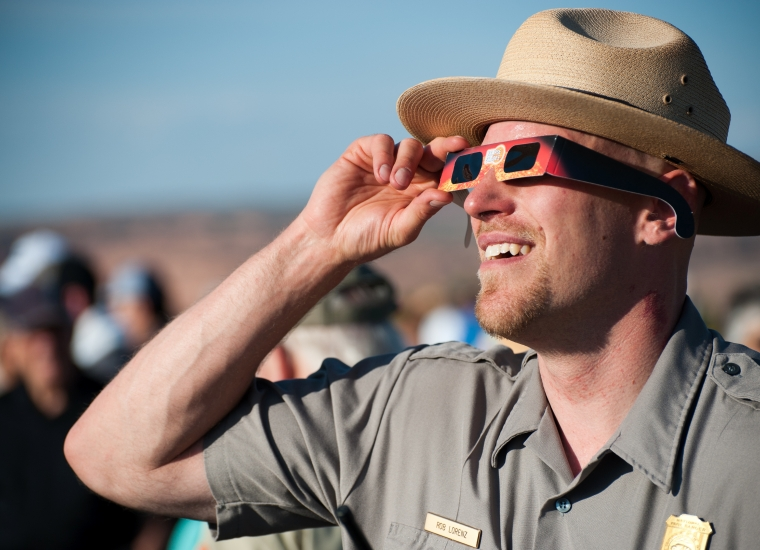 Park ranger looking through solar eclipse glasses at Arches National Park