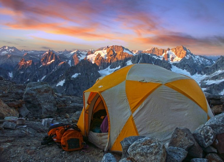 Tent surrounded by snow-covered mountains in North Cascades National Park