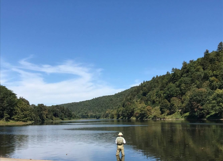 A man standing in a lake fly fishing at Upper Delaware Scenic & Recreational River