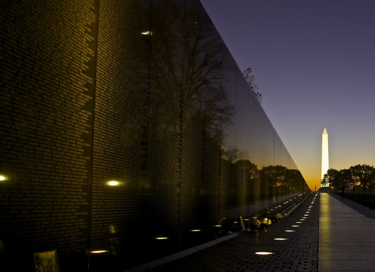 Vietnam Memorial Wall with the Washington Monument in the back at night