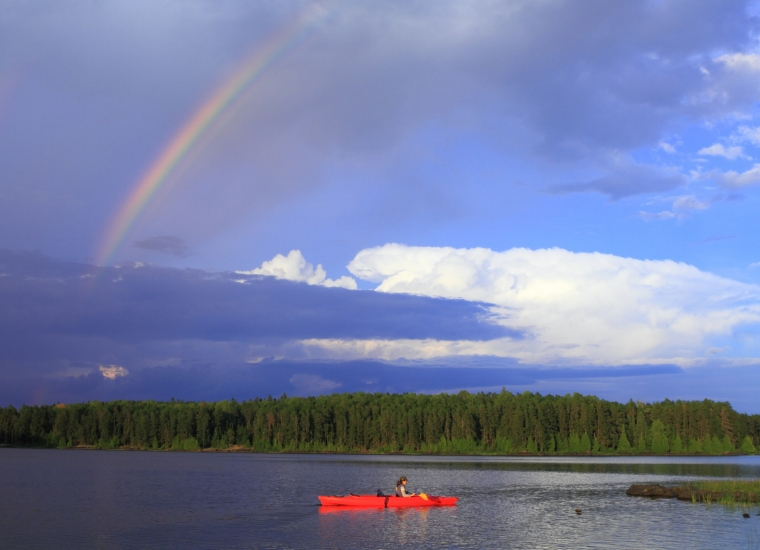 Woman in a red canoe on a lake with a rainbow in the sky at Voyageurs National Park