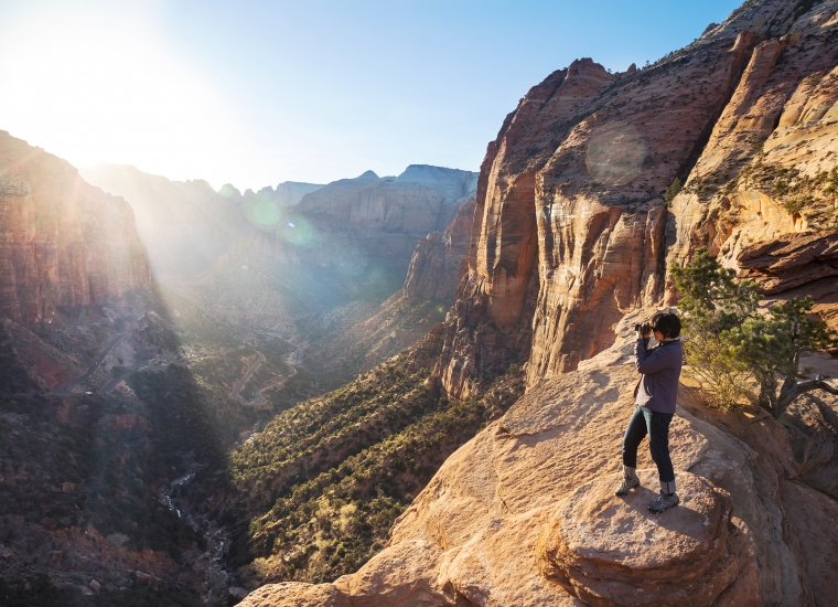 A visitor looks out on a vista and takes a picture in Zion National Park
