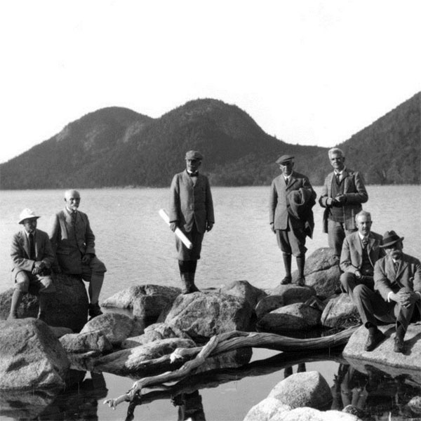 Men wearing suits stand and sit on coastal rocks posing for a portrait