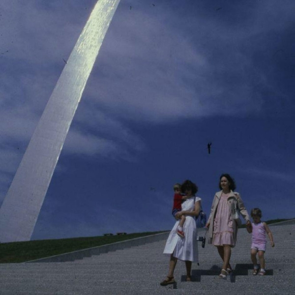 A family walks under a shining metal arch