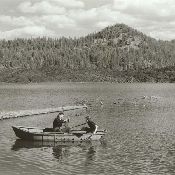 Two people fishing in a boat on a lake