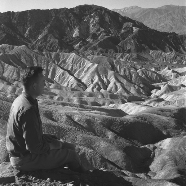 Man sits and looks across dunes at Death Valley