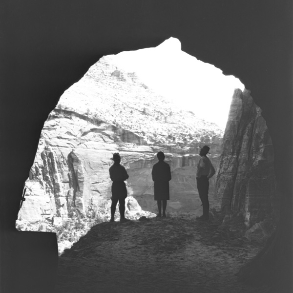 3 hikers standing at the edge of a cave