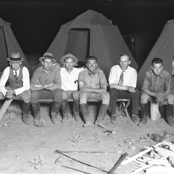 Men sitting in front of tents on a camping trip
