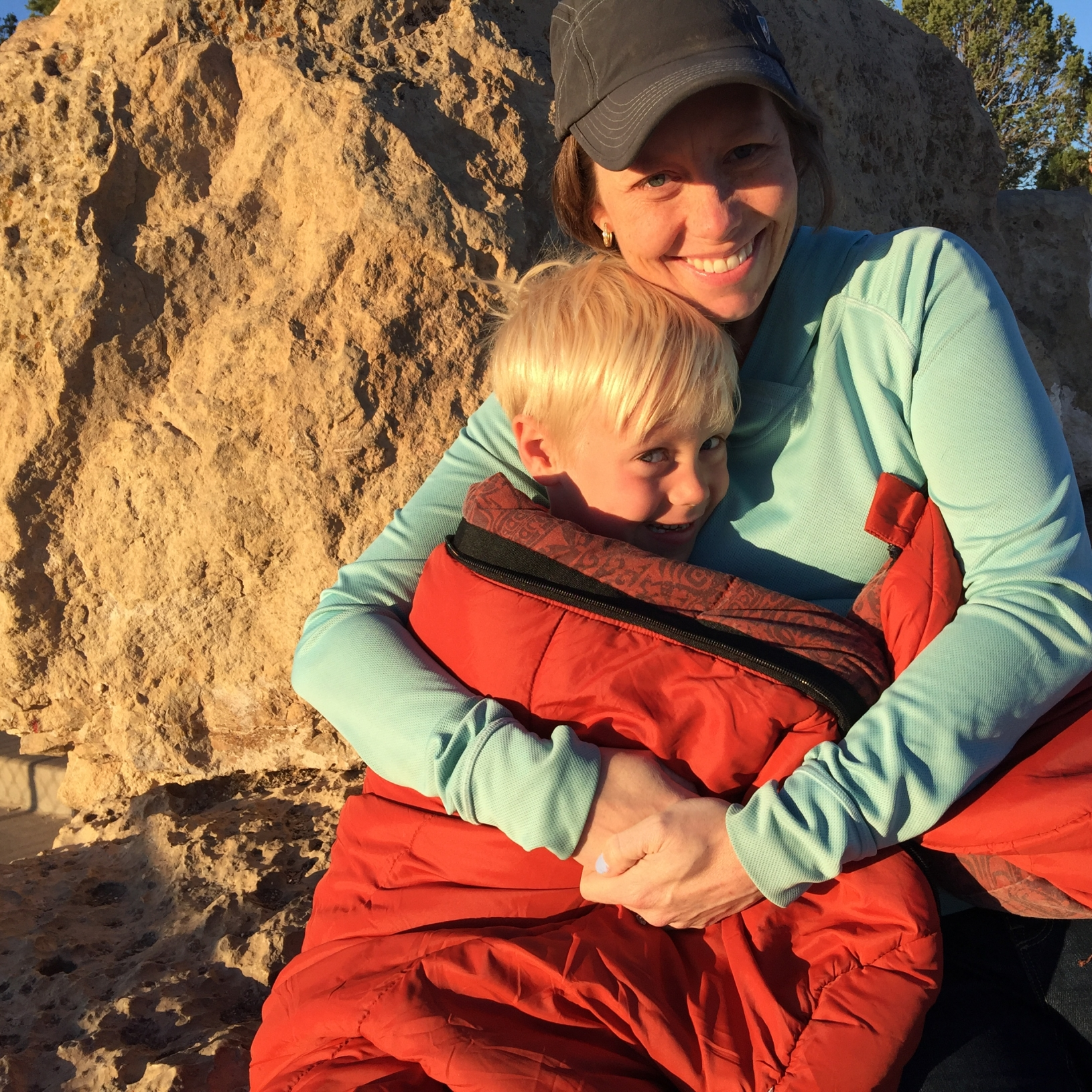 Mom and son hugging in front of a boulder, smiling toward the sun