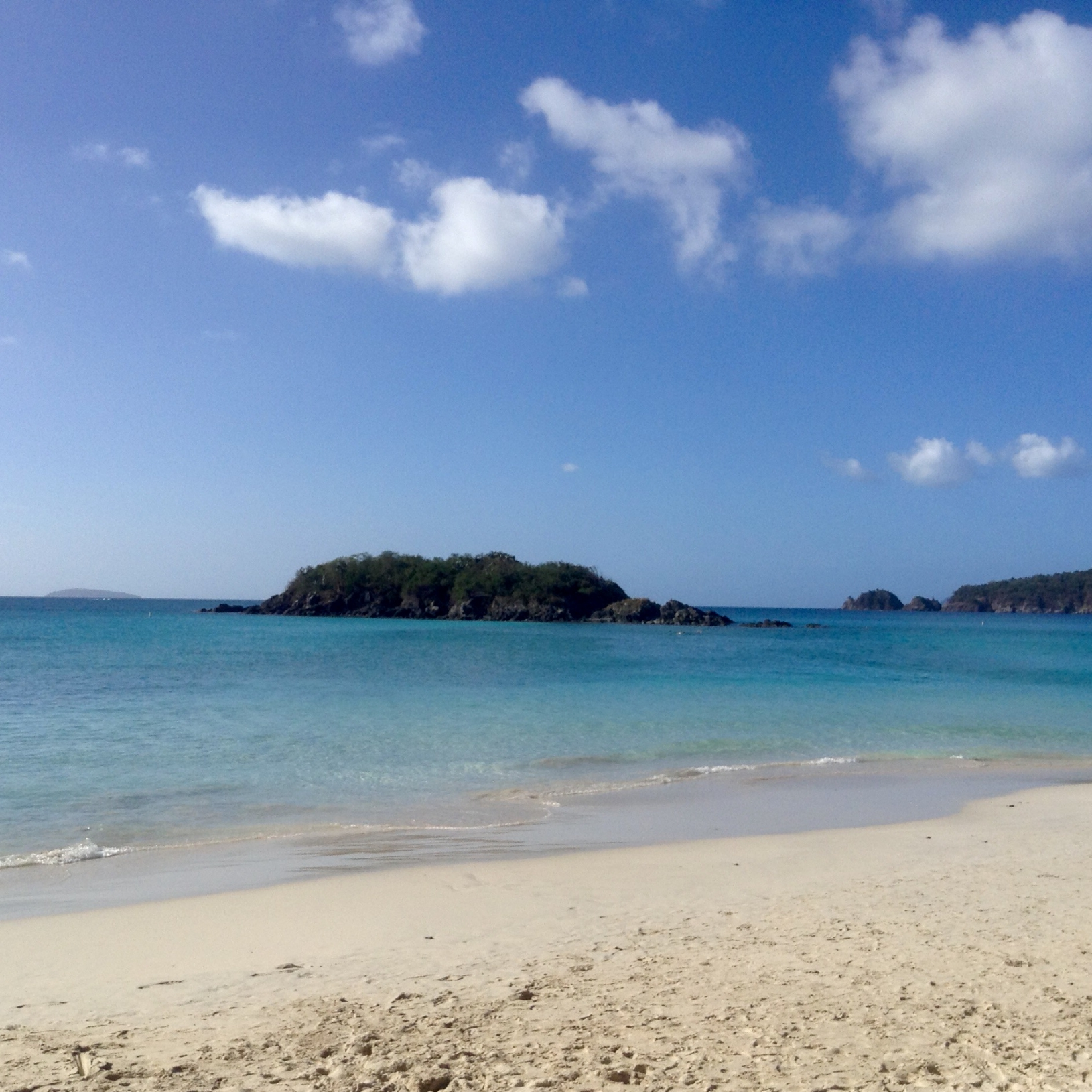 A view of Cinnamon Cay from Cinnamon Bay beach. The water is bright Aqua, the sky blue with a few little white clouds and the cay is craggy volcanic rock.