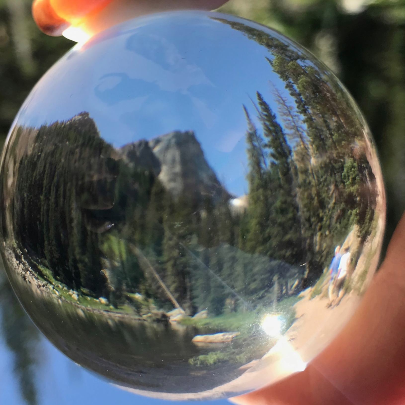 Dream Lake seen through a crystal ball as hikers make their way along the trail