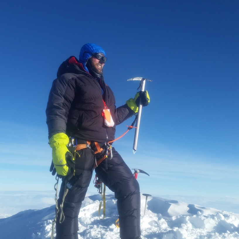 A climber on top of a snow covered peak