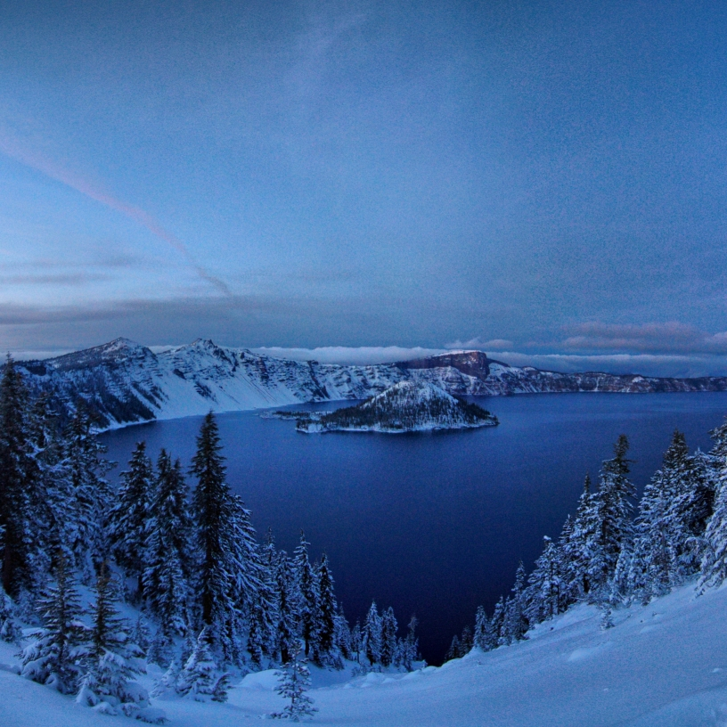 Blue-tinted overview of crater lake with evergreens covered in snow
