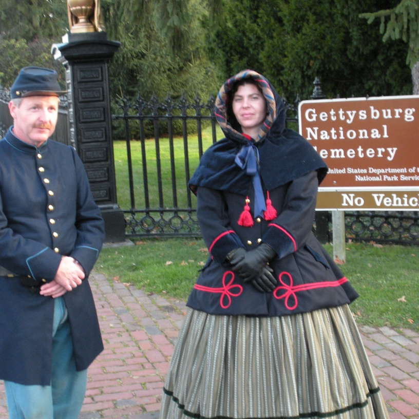 A period-appropriate-dressed man and woman in front of the Gettysburg sign.
