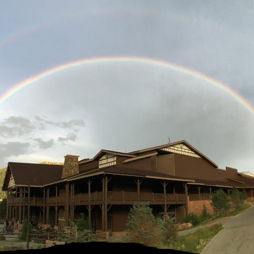 A double rainbow over a building in the Rocky Mountains